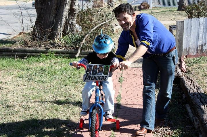 Homem com barba ensinando menino a andar de bicicleta