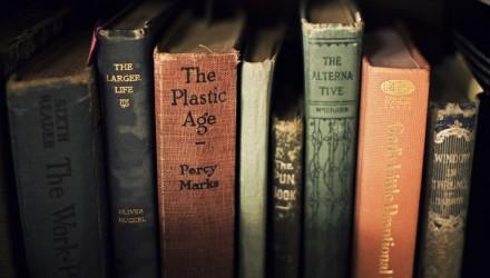 Livros lado a lado em prateleira, todos com aspecto velho