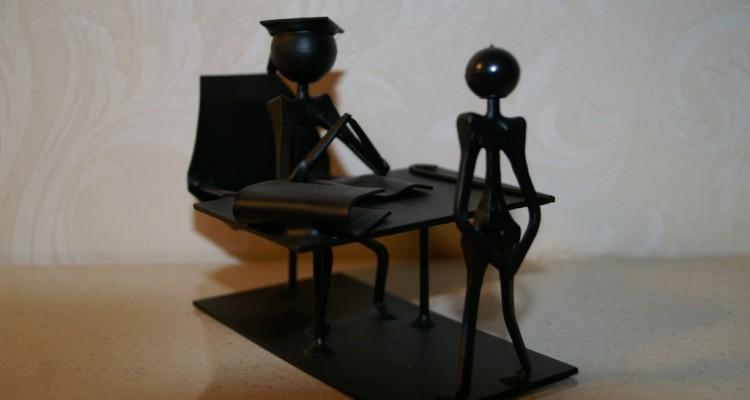 Pequenas esculturas em acrílico preto representando aluno e professor