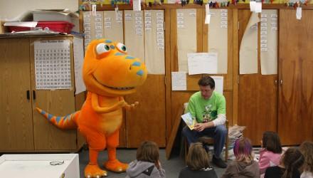 Professor lendo para alunos enquanto alguém fantasiado de dinossauro laranja entra na brincadeira