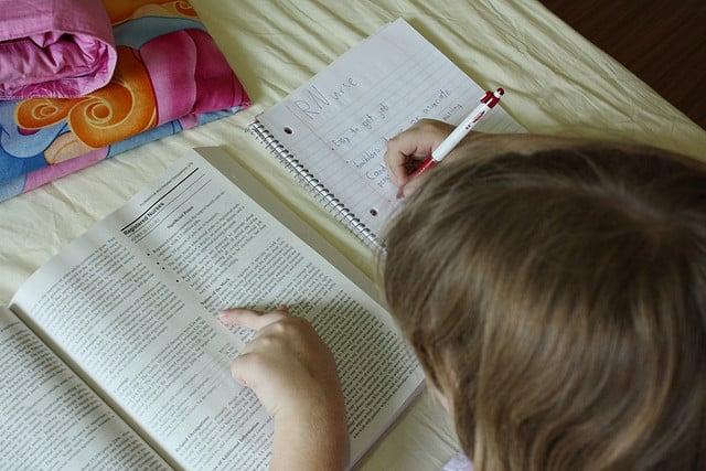 Criança pesquisando em livro e fazendo anotações em caderno