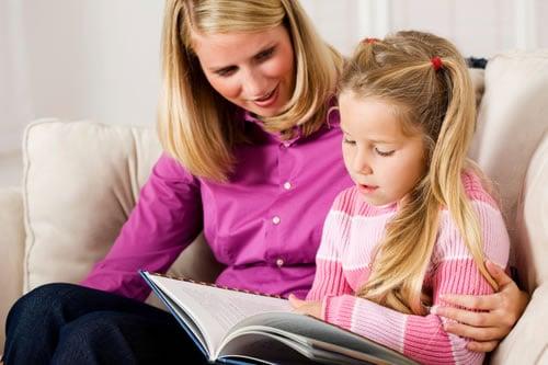 Mãe e filha lendo um livro para crianças