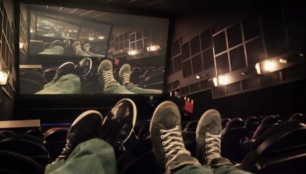 Pessoas no cinema, com os pés nas poltronas, olhando para a tela