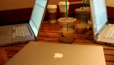 Mesa com milk shakes pela metade, com 3 notebooks da marca Apple, dois abertos, um fechado em primeiro plano.
