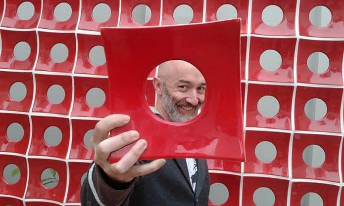 Alessandro Martins segurando um objeto vermelho com um furo no meio, que aparece em primeiro plano. Seu rosto, em segundo plano, aparece entre o furo do objeto.