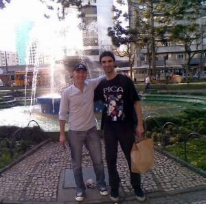 Alessandro Martins e André Gazole em frente a uma fonte, em uma praça da Cidade de Curitiba, no ano de 2010