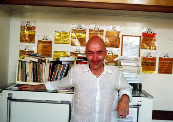 Alessandro Martins na Biblioteca Pote de Mel, escorado em uma mesa cheia de livros, de camisa branca.