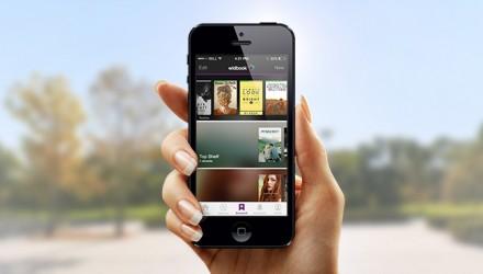 Uma mão segurando um smartphone com capas de livros na tela. Atrás, uma paisagem natural, com um lago.