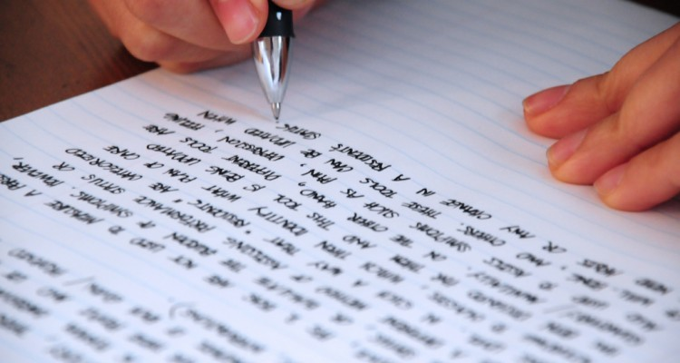 Papel em branco com mão direita escrevendo à caneta preta. Papel já preenchido