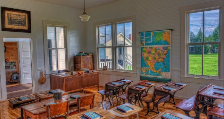 Ambiente de sala de aula com livros sobre as carteiras e um mapa pendurado na parede ao fundo