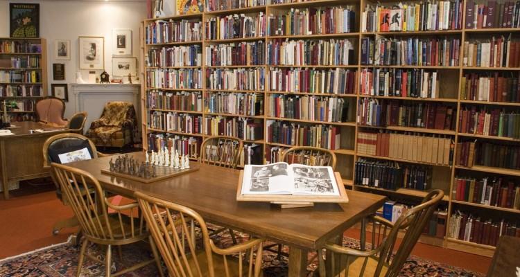 Sala com grande estante de livros atrás de mesa de madeira com livro e tabuleiro de xadrez à mostra