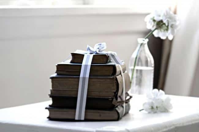 Livros antigos empilhados em forma de pirâmide amarrados por uma fita, formando um laço