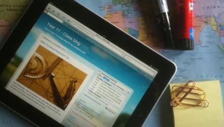 Tablet em cima da mesa de um professor, com um mapa estendido ao fundo