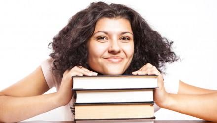 Estudante apoiada sobre livros e sorrindo