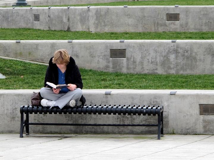 Pessoal lendo pacientemente em um banco público