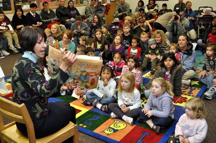 Professora dando aula com todos os alunos sentados e atentos