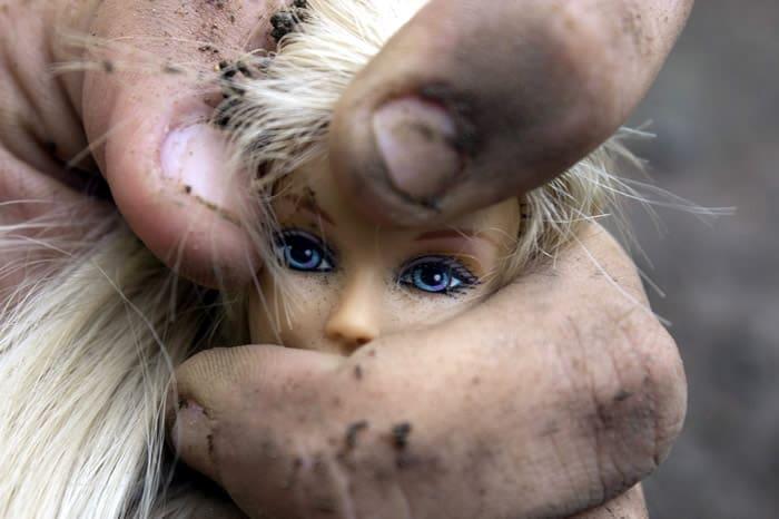 Cabeça de boneca sendo apertada por uma mão forte e suja