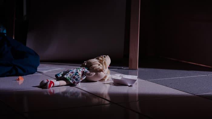 Boneca jogada no chão em ambiente sombrio